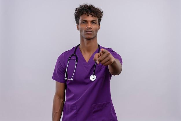 Ernsthafter junger gutaussehender dunkelhäutiger männlicher arzt mit lockigem haar in violetter uniform mit stethoskop, das mit dem zeigefinger auf die kamera auf weißem hintergrund zeigt