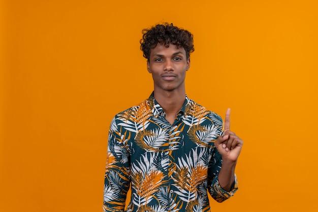 Ernsthafter junger gutaussehender dunkelhäutiger mann mit lockigem haar im bedruckten hemd der blätter, das eine geste mit zeigefinger auf einem orangefarbenen hintergrund macht