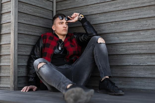 Ernsthafter junger hipster-mann mit einer stilvollen frisur mit sonnenbrille in einer trendigen rot karierten jacke in grau zerrissenen jeans in schwarzen turnschuhen entspannt sich in der nähe eines holzgebäudes
