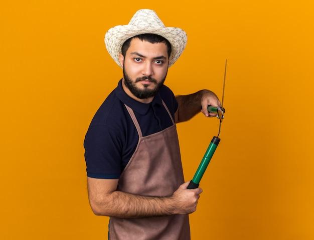 Ernsthafter junger kaukasischer männlicher gärtner, der gartenhut hält, der gartenschere lokalisiert auf orange wand mit kopienraum hält