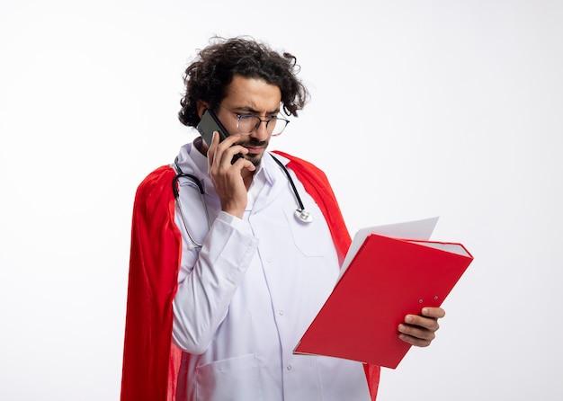 Ernsthafter junger kaukasischer superheldenmann in der optischen brille, die arztuniform mit rotem umhang und mit stethoskop um den hals trägt, das am telefon spricht und dateiordner mit kopienraum betrachtet