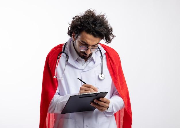 Ernsthafter junger kaukasischer superheldenmann in der optischen brille, die arztuniform mit rotem umhang und mit stethoskop um hals trägt, schreibt mit bleistift in zwischenablage auf weißer wand mit kopienraum
