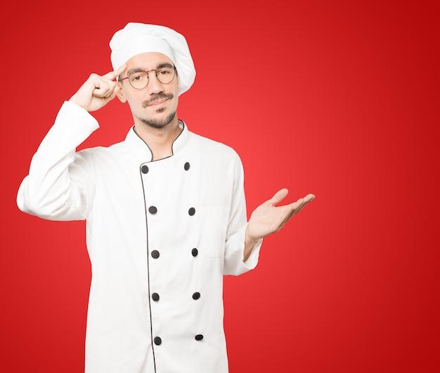 Ernsthafter junger koch, der eine geste der konzentration tut