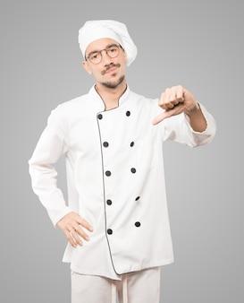 Ernsthafter junger koch, der eine geste der niederlage tut