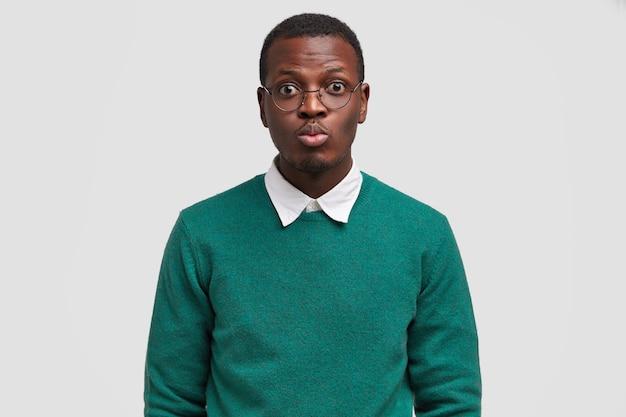 Ernsthafter junger männlicher hipster rundet lippen für kuss, hat datum mit frau, trägt runde brille, gekleidet im grünen pullover, lokalisiert über weißem hintergrund