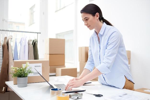 Ernsthafter junger manager, der sich auf die arbeit über online-bestellungen von kunden konzentriert, während er laptop-anzeige betrachtet