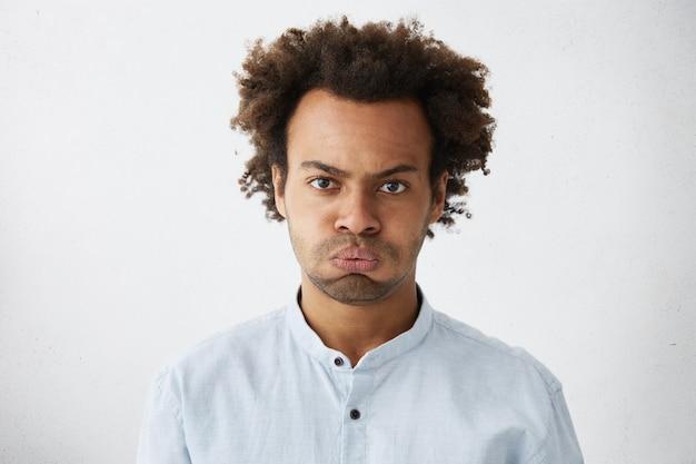 Ernsthafter junger manager mit afro-frisur mit gerunzelter stirn