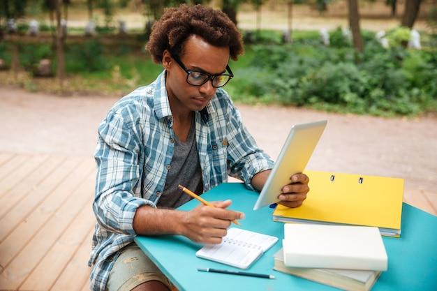 Ernsthafter junger mann, der im park schreibt und lernt