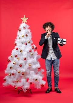 Ernsthafter junger mann, der sein geschenk hält, das schweigengeste macht, das nahe geschmücktem weißem weihnachtsbaum steht