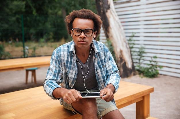 Ernsthafter junger mann in den gläsern und in den kopfhörern mit tablette, die im park sitzen