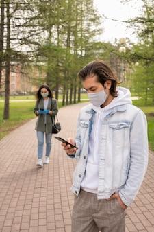 Ernsthafter junger mann in der freizeitkleidung, die im öffentlichen park steht und im telefon scrollt