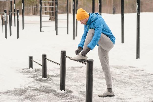 Ernsthafter junger mann in der grauen sporthose, die fuß auf stange hält und sportschuh am trainingsplatz im winter bindet