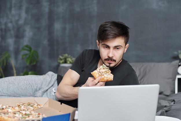 Ernsthafter junger mann mit dem schwarzen schnurrbart, der auf bett liegt und pizza isst, während film auf laptop in selbstisolation sieht