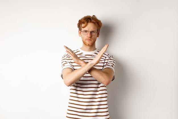 Ernsthafter junger mann mit stirnrunzelndem ingwerhaar, stop-geste zeigend, kreuz machen, um etwas schlechtes zu verbieten, nicht mit ihnen übereinstimmen, über weißem hintergrund stehend.