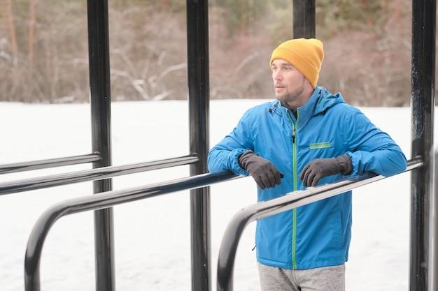 Ernsthafter junger mann mit stoppeln, die zwischen barren auf sportplatz im winter stehen und in die ferne schauen