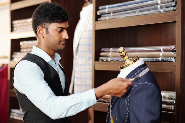 Ernsthafter junger professioneller schneider, der kragen der jacke auf schaufensterpuppe misst, wenn er im atelier arbeitet