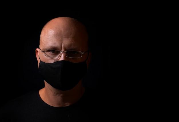 Ernsthafter kahlköpfiger mann mittleren alters mit brille, mit einer schwarzen medizinischen maske von covid 19 auf einem schwarzen hintergrund