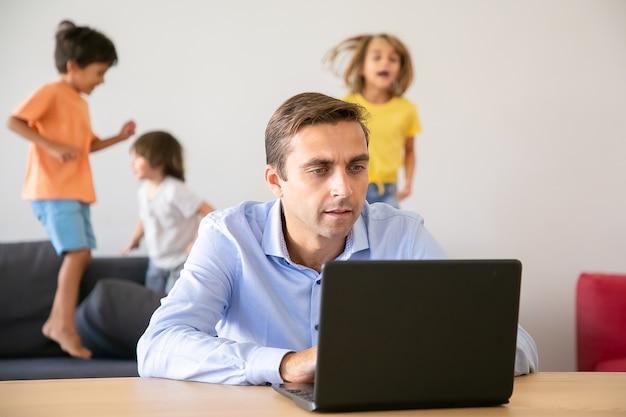 Ernsthafter kaukasischer vater, der über laptop und kinder springend arbeitet. konzentrierter vater, der computer und kinder benutzt, die auf sofa spielen. selektiver fokus. konzept für kindheit und digitale technologie