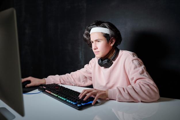 Ernsthafter kerl mit kopfhörern um den hals, der vor computerbildschirm sitzt, während er sich auf netzwerk in dunklem raum konzentriert