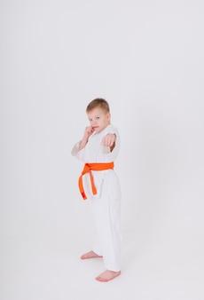 Ernsthafter kleiner junge in einem weißen kimono mit einem orangefarbenen gürtel steht in voller höhe in einer pose auf einer weißen wand