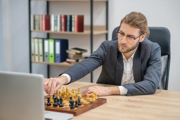 Ernsthafter kluger junger bärtiger mann im geschäftsanzug, der schach vor laptop im büro spielt