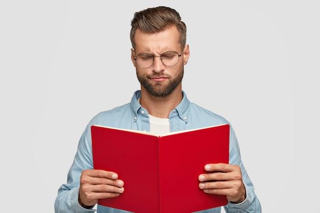 Ernsthafter kluger junger männlicher lehrer mit trendigem haarschnitt, trägt rotes buch, lose zögernd