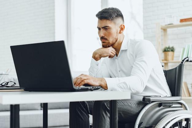 Ernsthafter konzentrierter behinderter im rollstuhl, der seinen laptop für die arbeit / arbeitssuche im internet benutzt