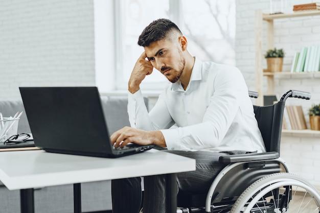 Ernsthafter konzentrierter behinderter im rollstuhl, der seinen laptop für die arbeitssuche im internet benutzt