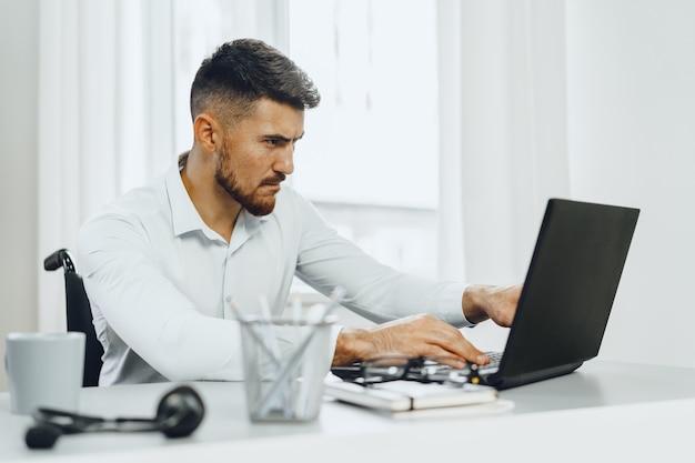 Ernsthafter konzentrierter behinderter mann im rollstuhl, der seinen laptop für die arbeitssuche im internet benutzt