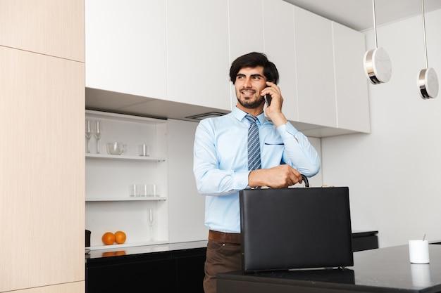 Ernsthafter konzentrierter junger geschäftsmann an der küche, der koffer hält, der durch handy spricht.