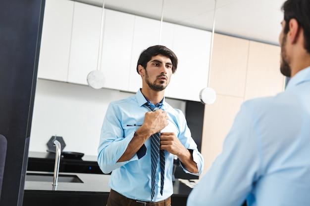 Ernsthafter konzentrierter junger geschäftsmann an der küche, die spiegel betrachtet.