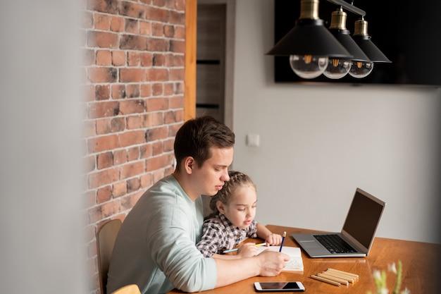 Ernsthafter konzentrierter junger vater, der mit geräten am tisch sitzt und herzen in notizbuch mit tochter zu hause zeichnet