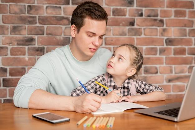 Ernsthafter konzentrierter junger vater im pullover, der am tisch sitzt und bild mit tochter zeichnet, kleines mädchen, das vater ansieht