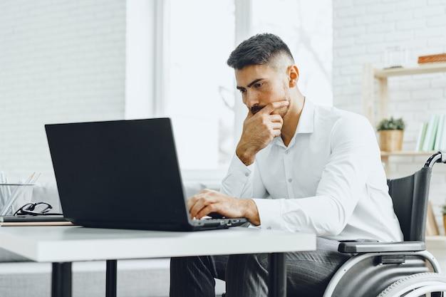 Ernsthafter konzentrierter mann im rollstuhl, der seinen laptop für arbeit / arbeitssuche im internet benutzt