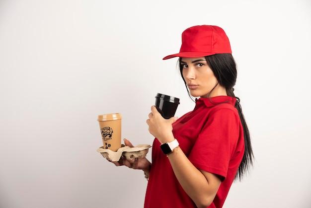 Ernsthafter kurier, der mit zwei tassen kaffee auf weißem hintergrund aufwirft. hochwertiges foto