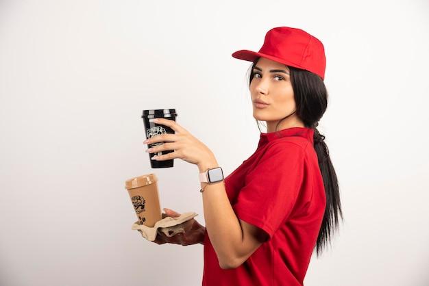 Ernsthafter kurier, der mit zwei tassen kaffee aufwirft. hochwertiges foto