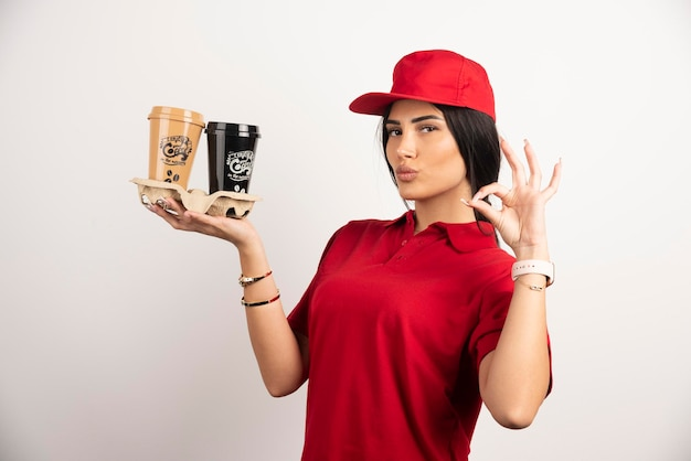 Ernsthafter kurier, der ok zeichen macht, während kaffee zum mitnehmen hält. hochwertiges foto