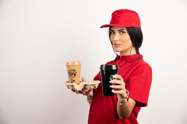 Ernsthafter kurier, der zwei tassen kaffee auf weißem hintergrund zeigt. hochwertiges foto