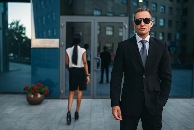 Ernsthafter leibwächter in anzug und sonnenbrille
