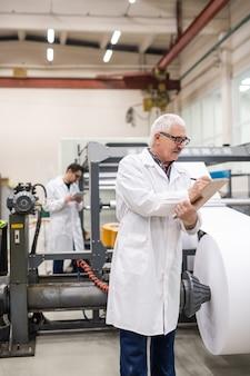Ernsthafter leitender inspektor im weißen kittel, der notizen in papier macht, während druckausrüstung im werk analysiert