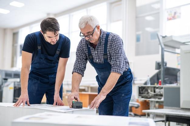 Ernsthafter leitender spezialist, der jungen arbeitern zeigt, wie man gedruckte papiere in der druckerei stempelt