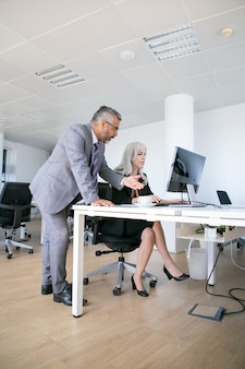 Ernsthafter männlicher chef, der mit weiblichem manager an ihrem arbeitsplatz spricht, während sie am computer arbeitet. geschäftskommunikationskonzept