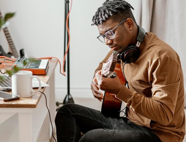 Ernsthafter männlicher musiker zu hause, der gitarre spielt und mit laptop mischt