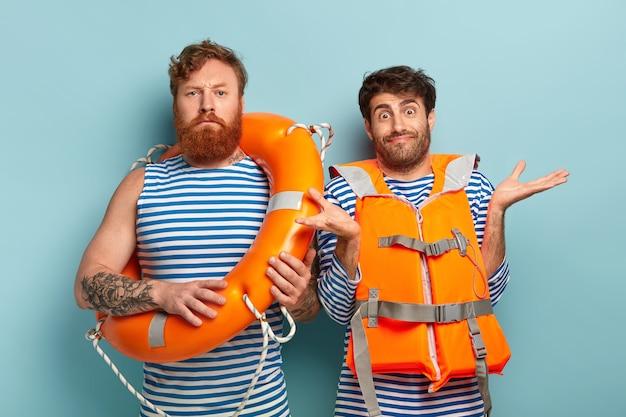 Ernsthafter männlicher schwimmlehrer mit rettungsleine, zweifelhafter auszubildender trägt orangefarbene weste, breitet hände aus