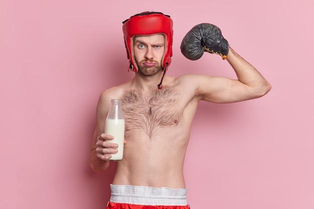 Ernsthafter mann boxer mit dünnem körper trägt boxhandschuhe und hut hebt arm zeigt muskeln trinkt milch für starken bizeps zeigt seine stärke und kraft. sport- und motivationskonzept