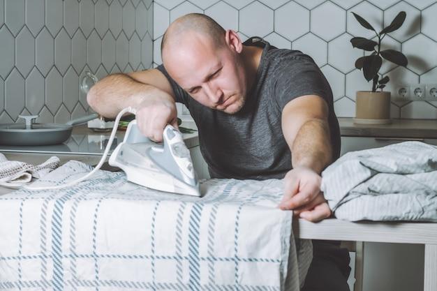 Ernsthafter mann bügelt bettwäsche vater ist mit hausarbeiten beschäftigt