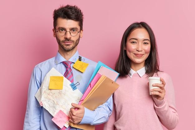 Ernsthafter mann büroangestellter hält ordner trägt formelles hemd mit angebrachten aufklebern, um daran zu erinnern, was zu tun ist. erfreute asiatische frau trinkt kaffee hilft gruppenmitglied bei kursarbeit oder startup-projekt