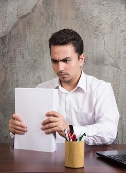 Ernsthafter mann, der blätter des papiers hält und am schreibtisch sitzt.