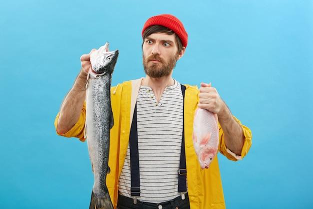 Ernsthafter mann, der zwei fische hält, die seinen fang betrachten