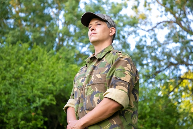 Ernsthafter mann in der militärischen tarnuniform, die im park steht und wegschaut.